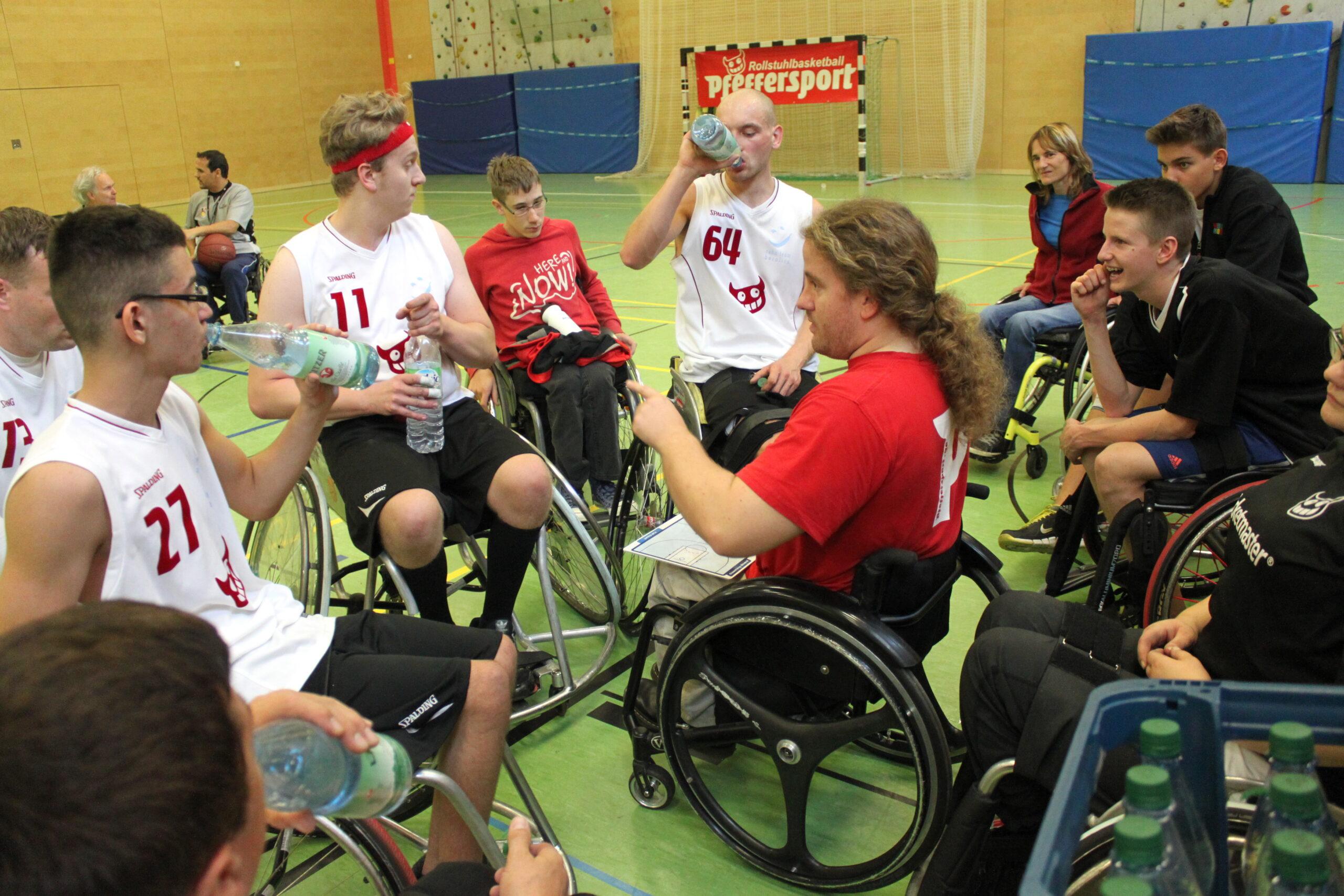 Christoph Pisarz mit mehreren anderen Rollstuhlfahrern in einer Trainingshalle. Er sitzt in der Mitte der anderen, hat eine Magnettafel in Form eines Basketball-Feldes auf dem Schoß und blickt zu den anderen. Einige von ihnen trinken aus Flaschen, Foto: Pfeffersport e. V.