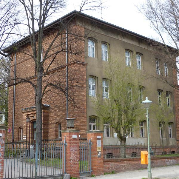 Das Deutsche Blindenmuseum Berlin-Steglitz in der Außenansicht. Ein Eisentor führt auf das Gelände auf dem ein dreistöckiges Backsteinhaus mit Bogenfenstern führt. Vor dem Haus steht eine junge Weide, Copyright Wikimedia Common, Foto: Muns.