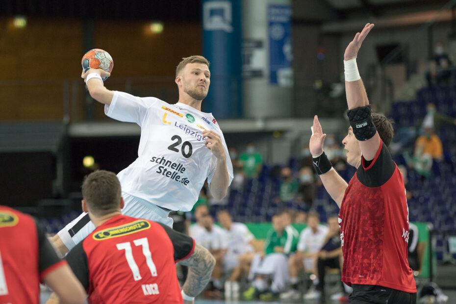 Handball mit Audiodeskription: Leipzigs Rückraum- und Nationalspieler Philipp Weber springt mit dem Ball in der rechten Hand hoch. Vor ihm hebt ein Abwehrspieler zur Verteidigung beide Arme. Weber mit entschlossenem Blick, Foto: Karsten Mann.