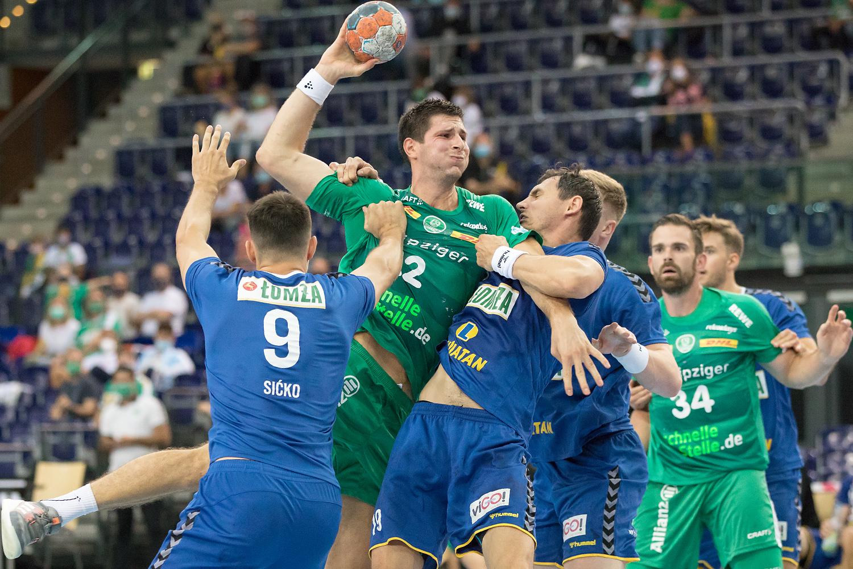Audiodeskription beim Handball: Ein Foto zeigt Handballspieler im Zweikampf. Ein Spieler im grün.weißen Trikot befindet sich im Sprung und hat den rechten Arm mit dem Ball in der Hand weit hochgehoben. Ein gegnerischer Spieler im blauen Trikot umklammert ihn und reißt an seinem Trikot, Foto: Karsten Mann.