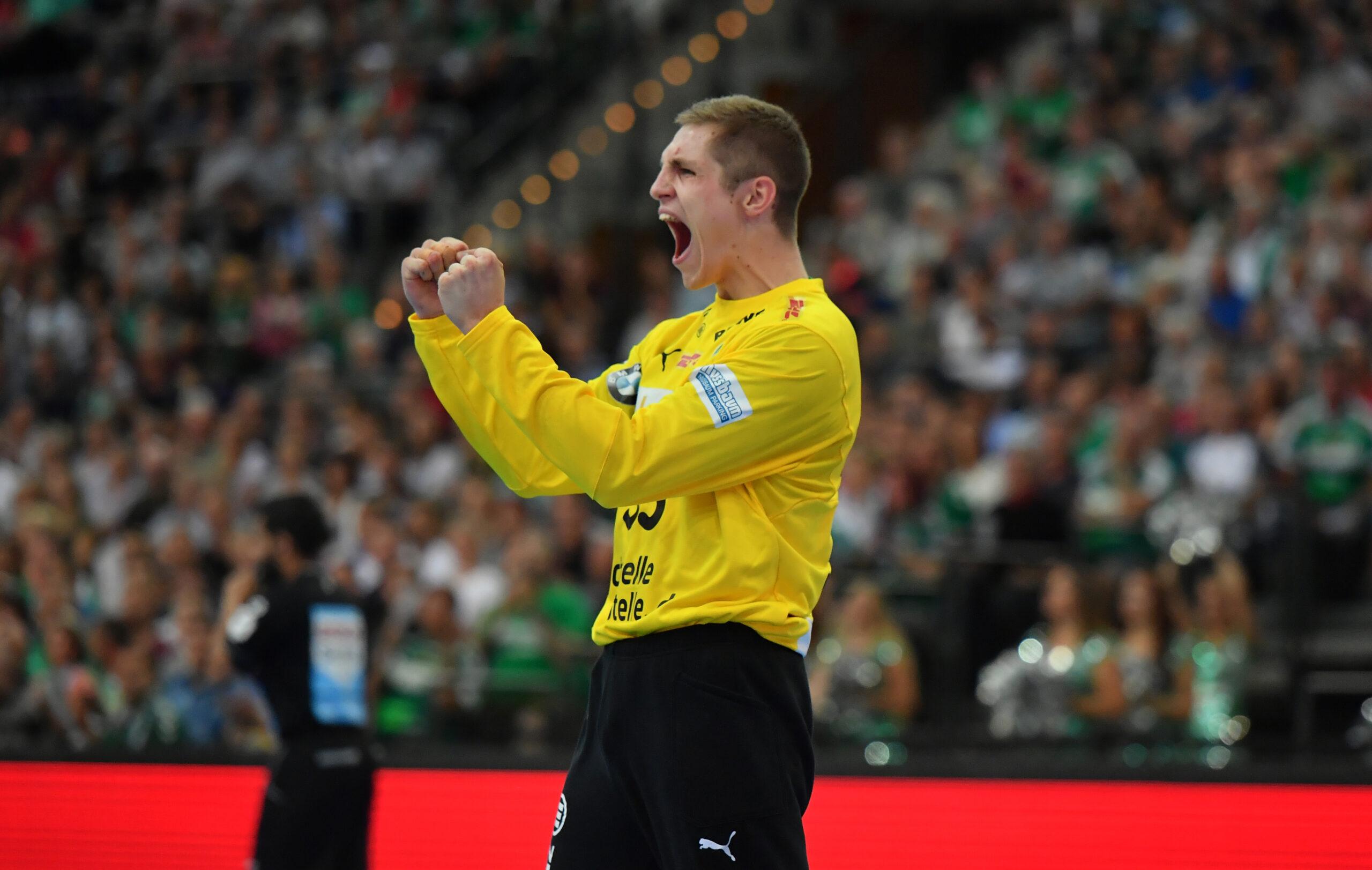 Handball mit Audiodeskription: Joel Birlehm – Handball-Torhüter – mit gelbem Trikot und langer schwarzer Hose. Verschwommen im Hintergrund sind zahlreiche Handballfans. Joel hat die Fäuste vor dem Körper geballt und den Mund von einem Jubelschrei weit geöffnet, Foto: Rainer Justen.