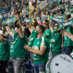 Handballfans in der Leipziger Arena. Sie tragen grüne Fanshirts und halten Schals in die Luft. Alle tragen Masken. Handball live mit Audiodeskription in Leipzig, Foto: Karsten Mann.