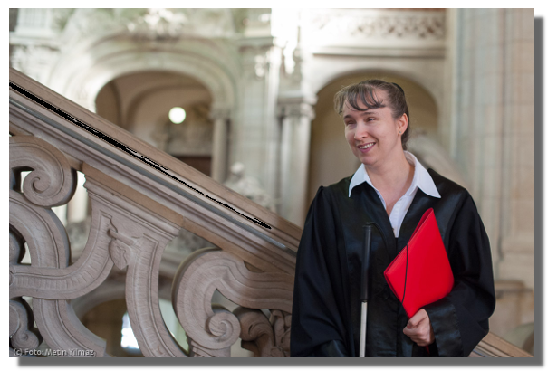 Die blinde Strafverteidigerin Pamela Pabst in Robe und mit einer Akte unter dem Arm. Sie steht neben einem verzierten Treppengeländer. Verschwommen im Hintergrund ist ein Gebäude mit hohen Decken und weiten Torbögen. Pamela Pabst lächelt in die Kamera, Fotorechte: Metin Yilmaz.