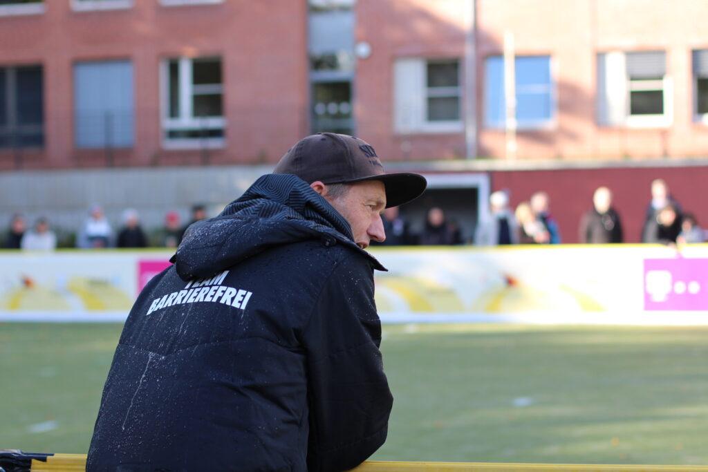"""Wolf Schmidt an der Bande eines Blindenfußballspielfeldes. Die Fotografie zeigt ihn aus der Rückenperspektive, aus seiner schwarzen Windjacke steht """"Team barrierefrei"""". Schmidt blickt leicht über die Spielfeldbande gelehnt nach rechts. Sein Mund ist geöffnet, er gibt Anweisungen. Auf dem Kopf trägt er ein braunes St. Pauli-Basecap. Im Hintergrund liegt ein Blindenfußball-Spielfeld mit grünem Kunstrasen. An der gegenüberliegenden Bandenseite sind verschwommen einige Zuschauerinnen und Zuschauer zu erahnen, Foto: Tomke Koop."""