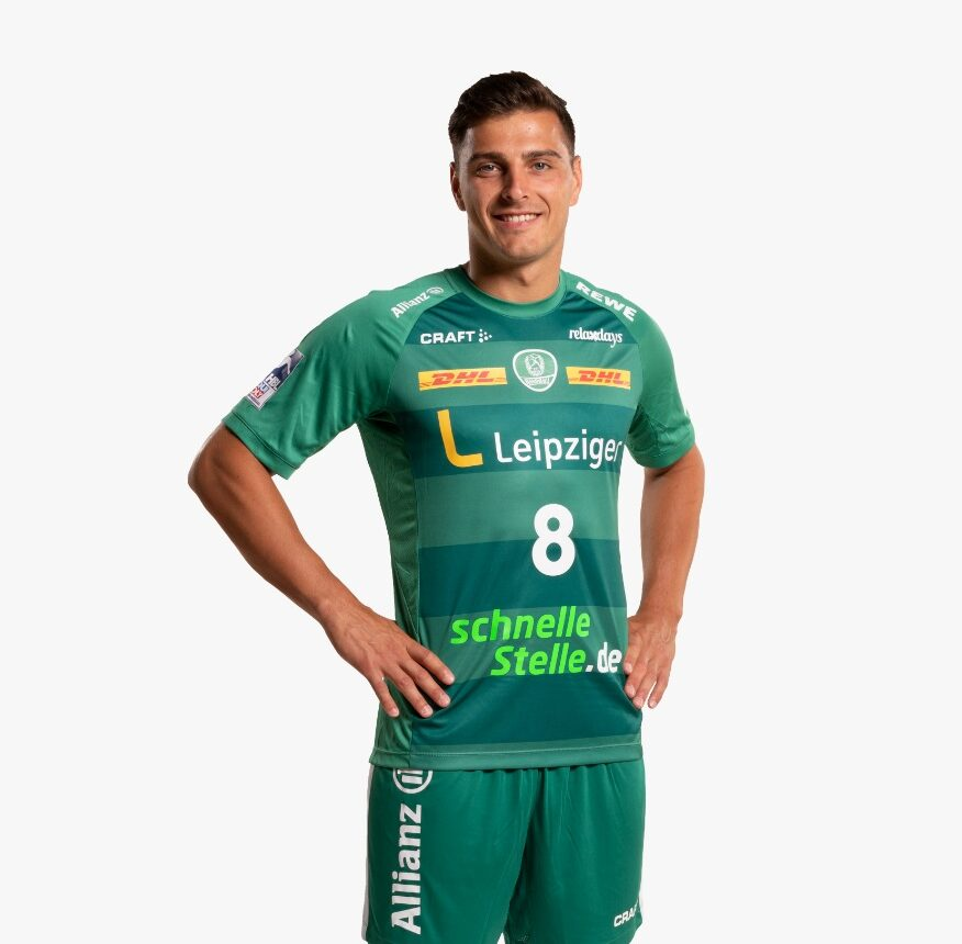 Der Handballspieler Lukas Krzikalla mit in die Hüften gestützten Händen. Er trägt ein grünes Trikot mit dem Logo des SC DHfK Leipzig, Foto: SC DHfK Handball.
