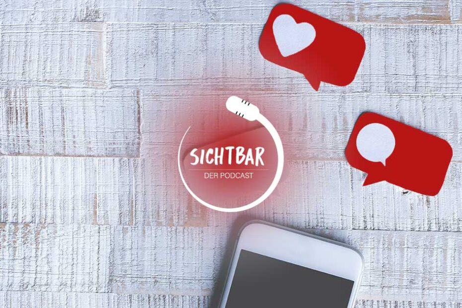 """SICHTBAR – Der Podcast: Dating-Apps für Sehbehinderte. Ein Farbfoto einer hellen Holzfläche. Auf dieser liegt im unteren Bildrand ein weißes iPhone. schräg darüber befinden sich zwei rote Sprechblasen, in denen jeweils ein weißes Herz und eine weiße Sprechblase abgebildet sind. In der Mitte des Fotos ist das Logo von SICHTBAR abgebildet. Dieses besteht aus einem zu einem Kreis geschwungenen Mikrofon, in dessen Mitte der Schriftzug """"SICHTBAR DER PODCAST"""" steht."""