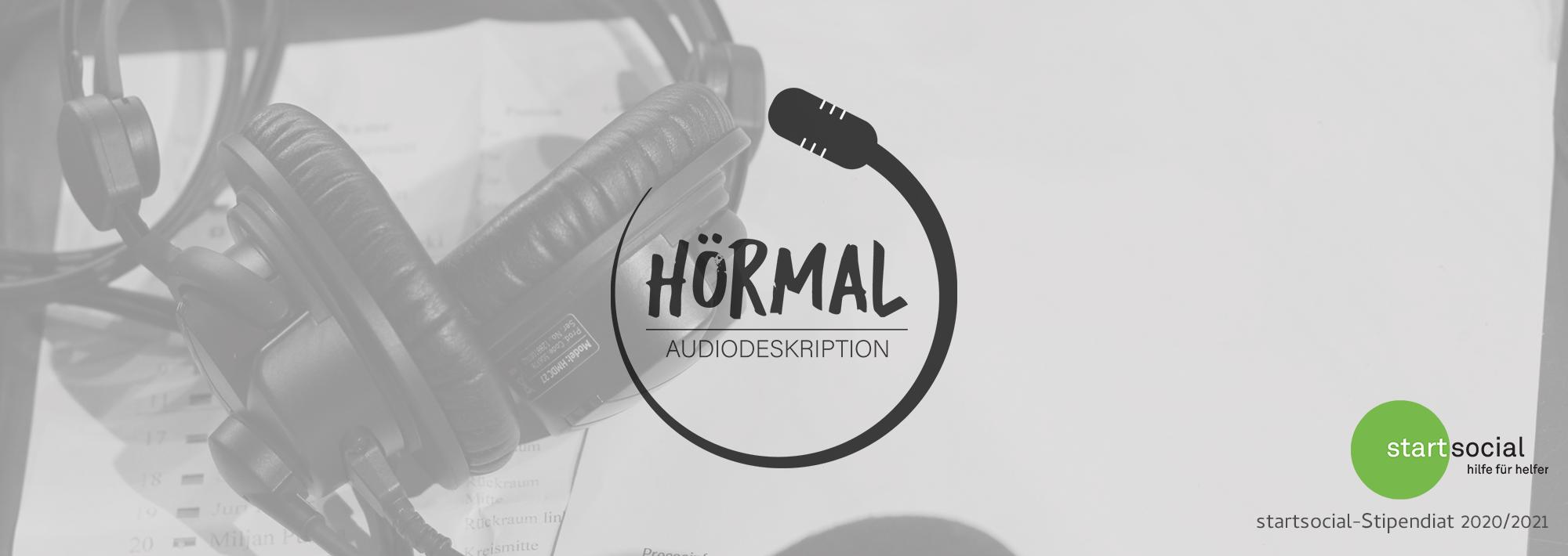 Das Banner besteht aus einem Foto-Hintergrund, der leicht transparent eingefärbt ist und Logos auf diesem Hintergrund. Der Hintergrund zeigt teile eine Sprech-Headsets für Audiodeskription-Spreacher, daneben liegen Notizzettel. Die Logos darauf sind in schwarz und grün eingefärbt. In der Mitte steht das Logo von HörMal Audiodeskription. Ein eckiger Schriftzug von einem langgezogenen Mikrofon umschlungen. Rechts unten befindet sich das startsocial-Logo. Darin steht: Startsocial – Hilfe für Helfer. Darunter: startsozial-stipendiat 2020/2021, Grafik: HörMal Audiodeskription und startsocial.