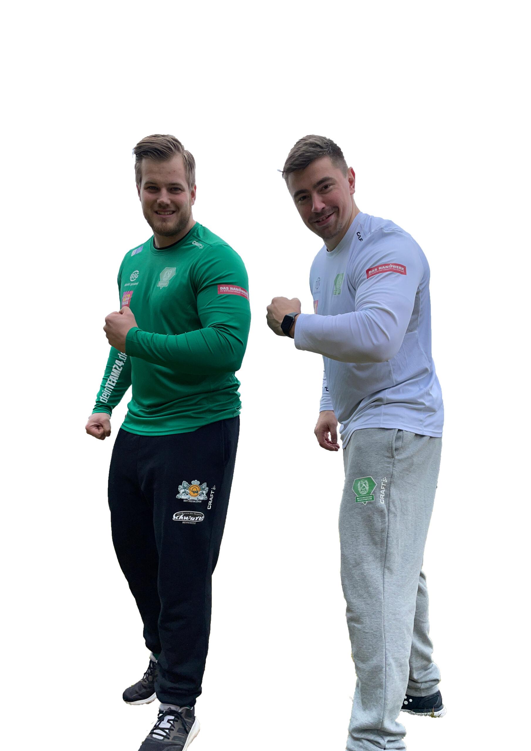 Die beiden Kugelstoßer Dennis Lemke (links) und David Storl (rechts) stehen seitlich nebeneinander und haben ihren linken Arm angewinkelt ausgestreckt. So wird ihr muskulöser Oberarm sichtbar. Beide lächeln.