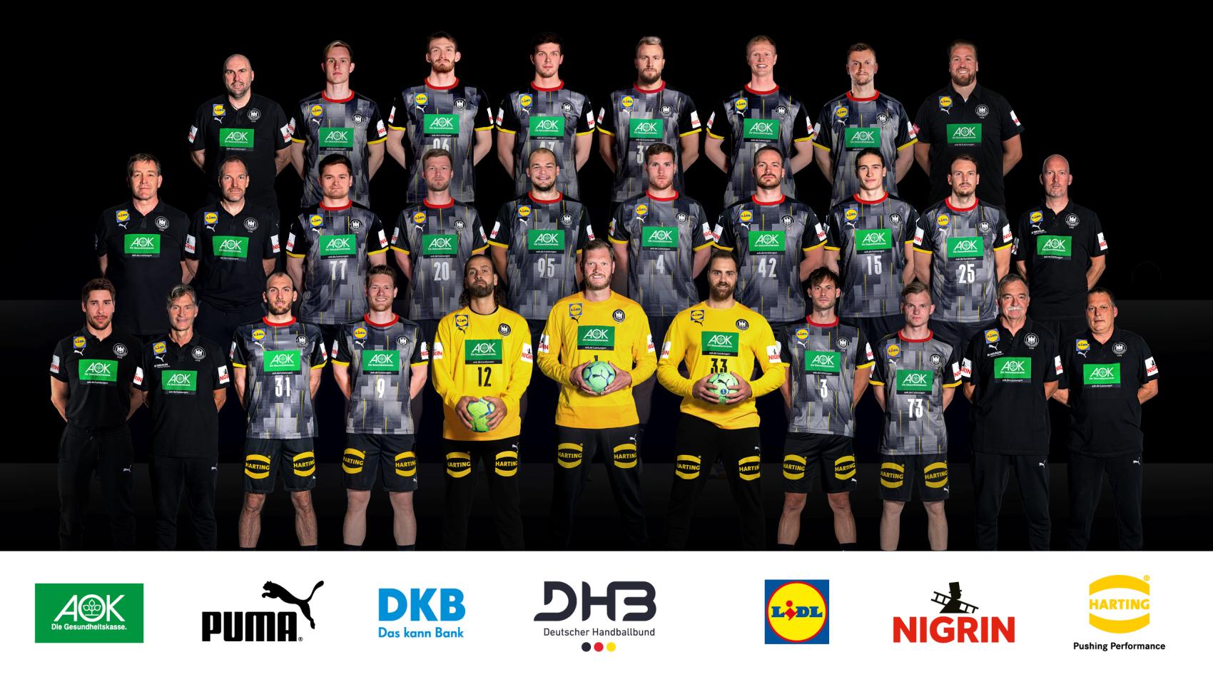 Ein Teamfoto der deutschen Handball-Nationalmannschaft. Die Spieler und Verantwortlichen stehen in drei Reihen hintereinander und nach oben versetzt. Sie tragen dunkle Trikots, die Feldspieler grau und die Verantwortlichen schwarz jeweils mit grünem Aufdruck. Die drei Torhüter stehen in der ersten Reihe vorn und tragen gelbe Trikots. Sie halten grüne Handbälle in den Händen. Foto: Sascha Klahn/DHB, kurz vor der Olympia-Qualifikation mit Audiodeskription.