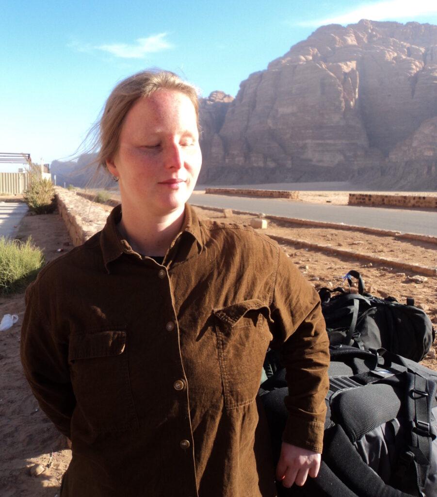 Svenja Fabian von Sonne beschienen steht Freien. Im Hintergrund ragt eine felsige Bergwand auf. Neben ihr steht ein gefüllter Wanderrucksack, Foto: Svenja Fabian.