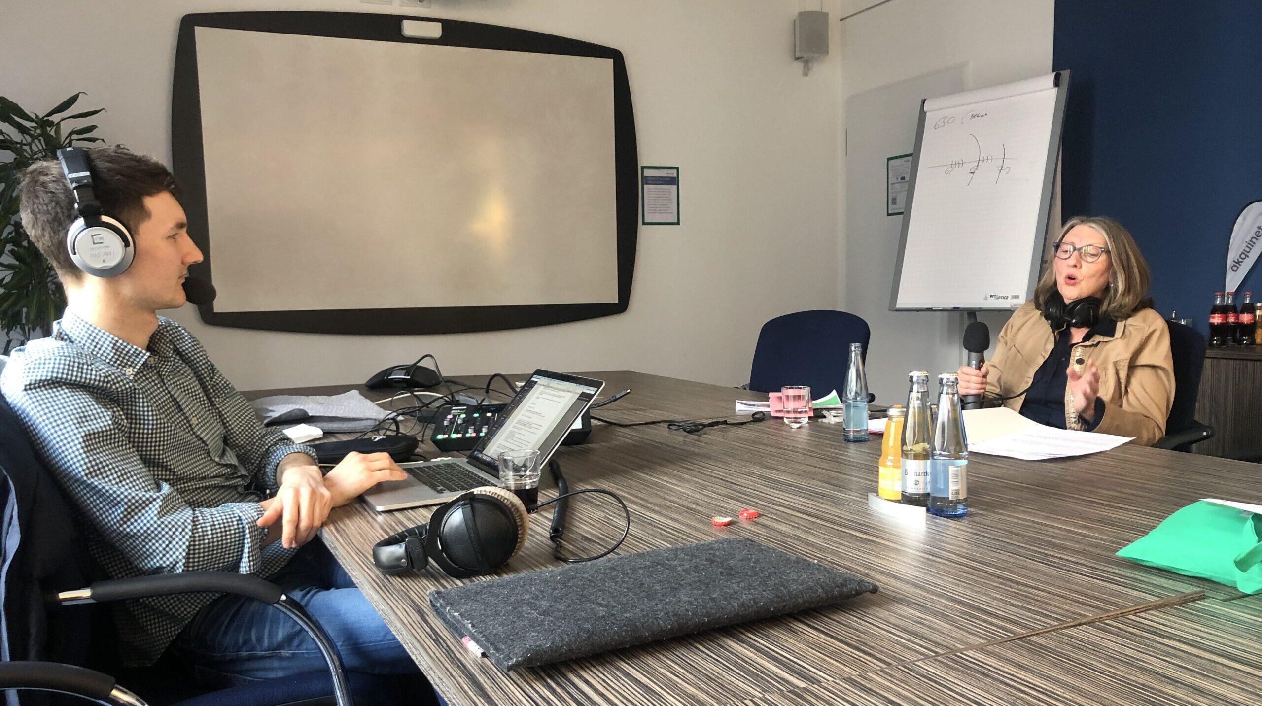 An einem breiten Konferenztisch sitzen am einen Ende Florian Eib und am anderen Susanne Klein. Beide haben Headsets auf dem Kopf und blicken sich an. Susanne Klein gestikuliert. Florian hat einen Laptop mit Text und ein Mischpult vor sich, Foto: Tomke Koop.