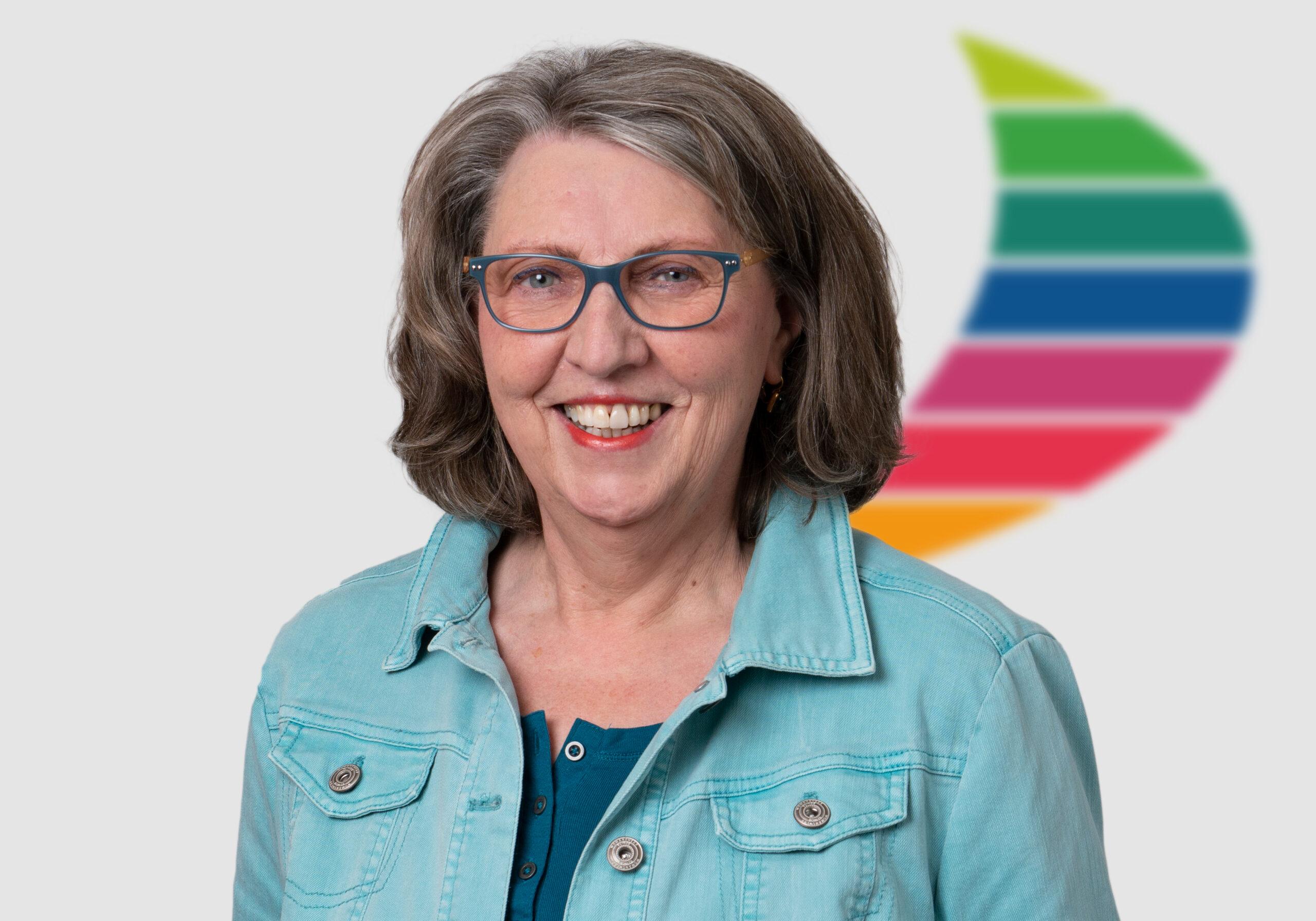 Gleichberechtigung im Berufsleben – Dafür setzt sich Susanne Klein ein. Das Portraitfoto zeigt sie lächelnd und mit Brille in einem dunkelblauen Top, darüber ein hellblaues Jeanshemd. Sie trägt schulterlange grau-melierte Haare. Im Hintergrund erscheint das buntgefärbte Logo von AKQUINET, Foto: AKQUINET.
