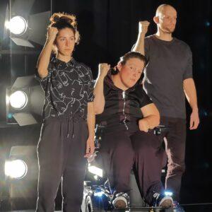 Tanzstück mit Audiodeskription: Das Farbfoto zeigt drei Personen im Zentrum des Bildes. Links eine stehende Frau, rechts daneben eine Frau im Elektro-Rollstuhl und ein stehender Mann. Alle drei tragen schwarze Kleidung und haben jeweils ihren rechten Arm im 90-Grad-Winkel mit geballter Faust nach oben. Sie schauen mit ernstem Gesicht geradeaus. Direkt hinter ihnen befinden sich drei helle Scheinwerfer und eine schwarze Wand.