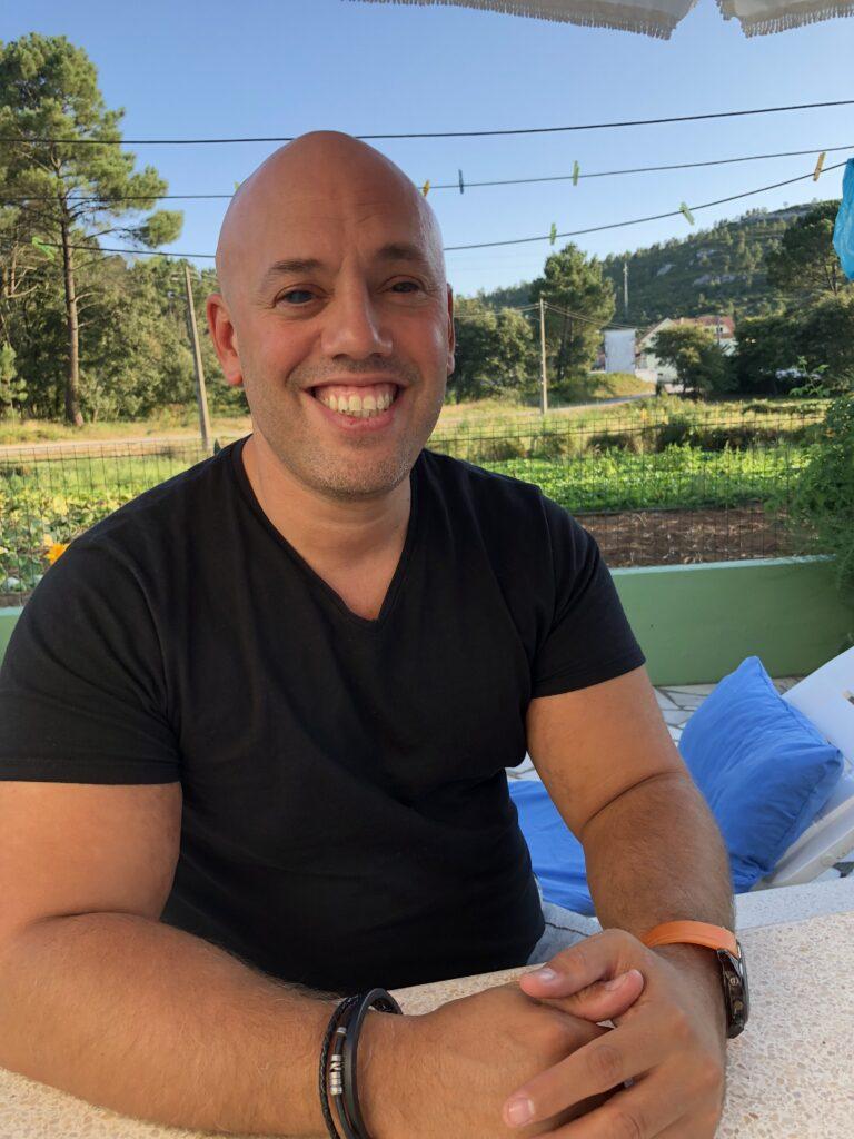 Ein Beispiel für berufliche Integration - Ein Portraitfoto von Lucas Carvalhana mit einem schwarzen T-Shirt. Er hat Glatze und lächelt breit. Im Hintergrund befinden sich einige Bäume und eine Wiese, Foto: AKQUINET.