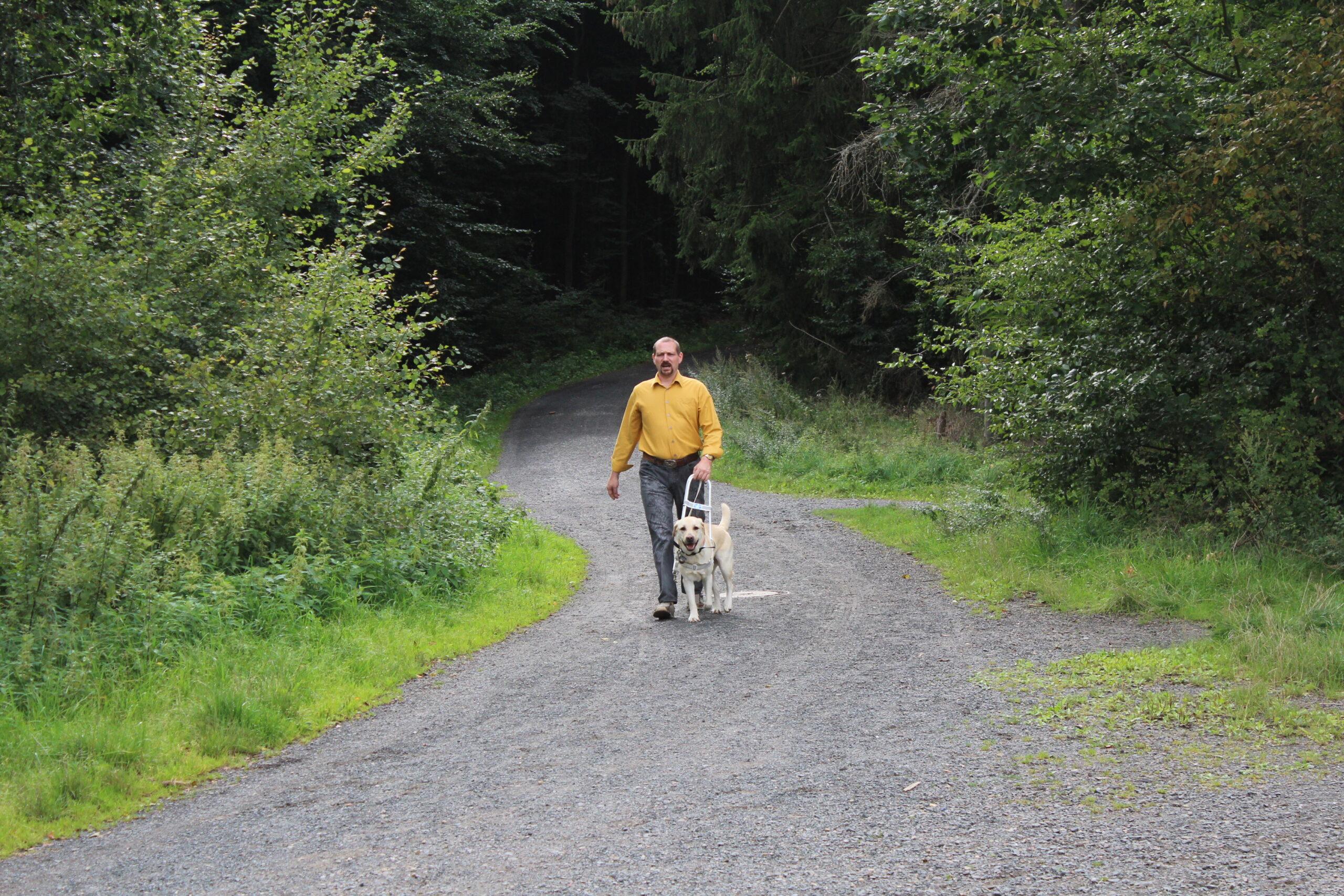 Marco Beyer geht mit seinem Blindenführhund einen Schotterweg entlang. Links und rechts ragen Bäume und Büsche auf, Bildrechte: Marco Beyer.