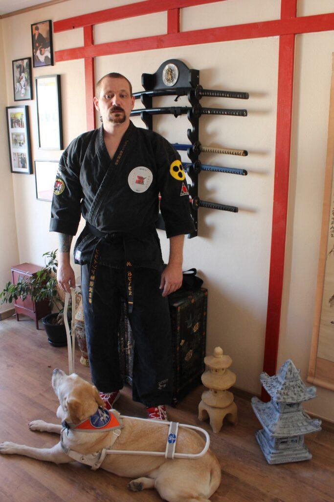 Marco Beyer steht hinter seinem liegenden Blindenhund. Er trägt einen schwarzen Kampfanzug. Im Hintergrund hängen Schwerter an der Wand, Bildrechte: Marco Beyer.