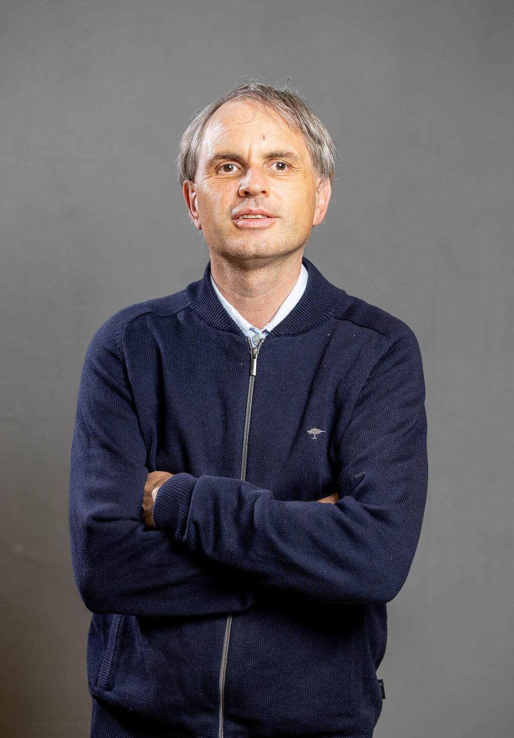 Eine Portraitaufnahme von Christof Müller. Er trägt eine blaue Strickjacke und hat seine Arme vor dem Körper verschränkt. Seine grauen Haare sind zu einem Scheitel frisiert, Foto: Christof Müller.