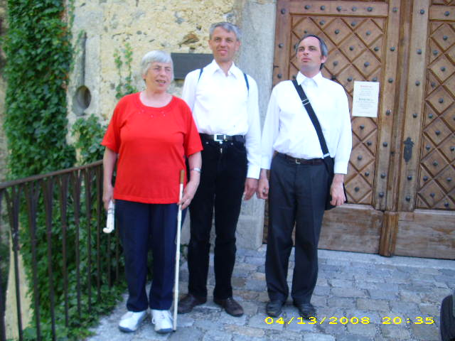 Eine grauhaarige mit Blindenstock, blauer Hose und rotem Oberteil steht neben zwei mittelalten Männern, die beide dunkle Hosen und dazu ein weißes Hemd tragen. Sie alle stehen vor einem doppelflüggen Holztor mit metallnen Türbeschlägen. Über der Wand neben der Tür hängen grüne Blätterranken herunter, Fotorechte: Christof Müller.